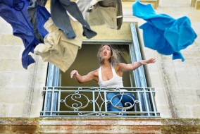 Woman throwing clothes by the window