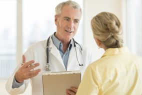 Senior doctor with clipboard explaining report to female patient in hospital