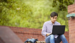 Young man in casual clothes sitting on the top step of an outdoor concrete stairway, working on a Dell Inspiron 14 3000 Series Touch or Non-Touch (Model 3441, 3442 or 3443) notebook computer.