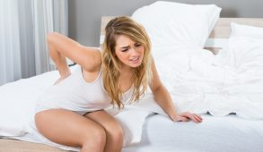 Woman Sitting On Bed Suffering From Back Pain