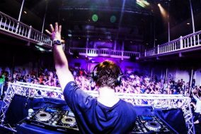 A DJ holding his left arm up in front of a packed dance floor