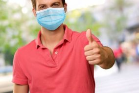 "Man wearing mask making ""thumbs up"" sign"