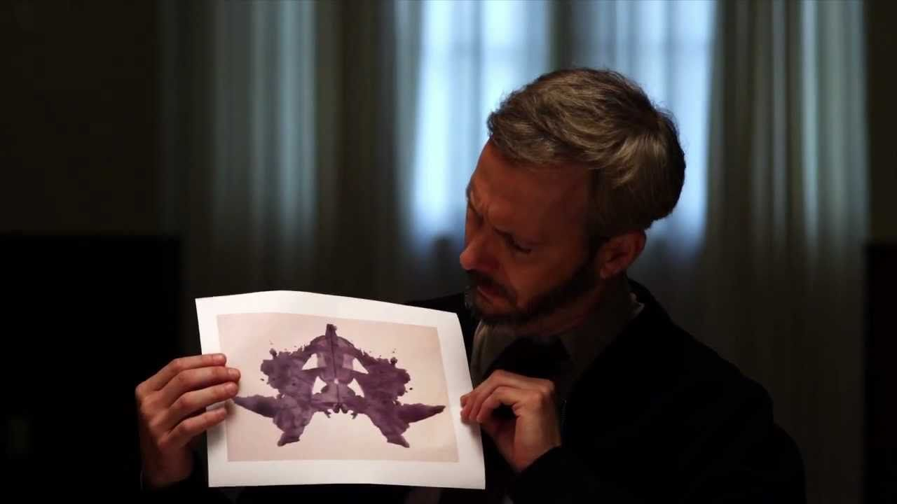 man holding an inkblot page