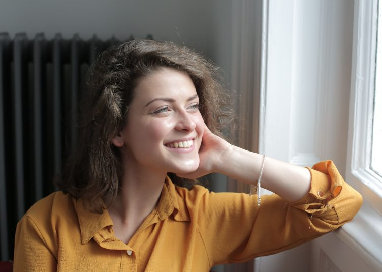 white woman in yellow shirt stares happily out of window