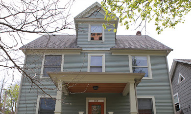 house with shirtless man in upper-floor window