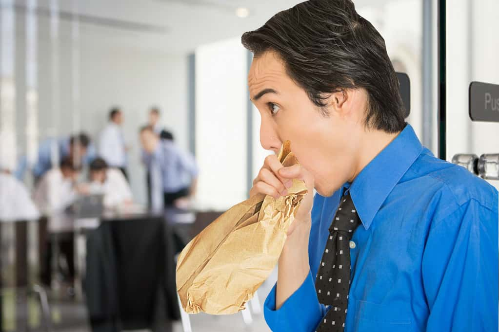 Man breathing into a paper bag frantically