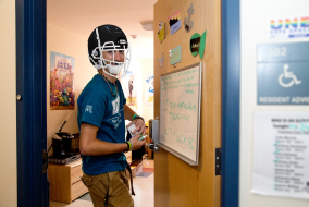 An RA in a dorm room wearing a football helmet