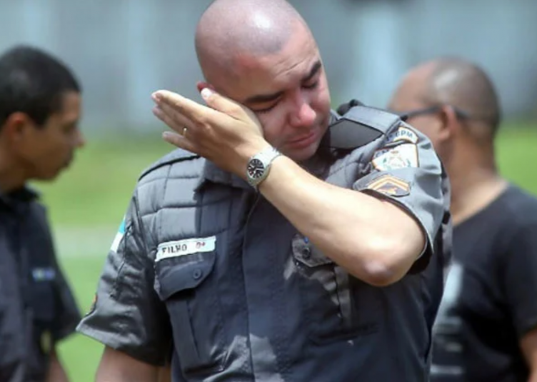 police officer using hand to wipe away tears
