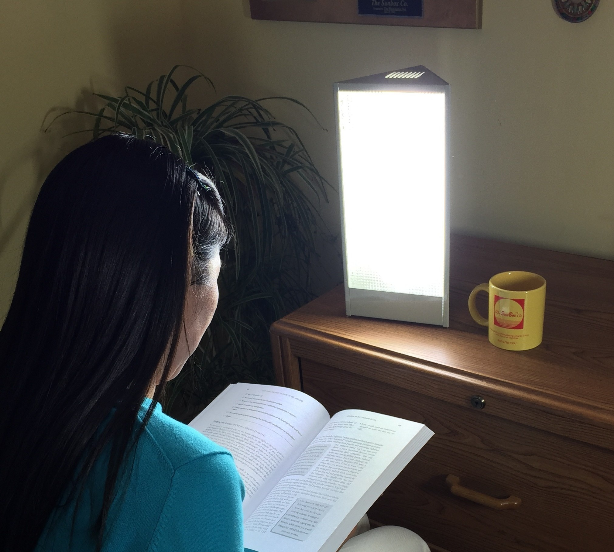 Woman reading by sun lamp