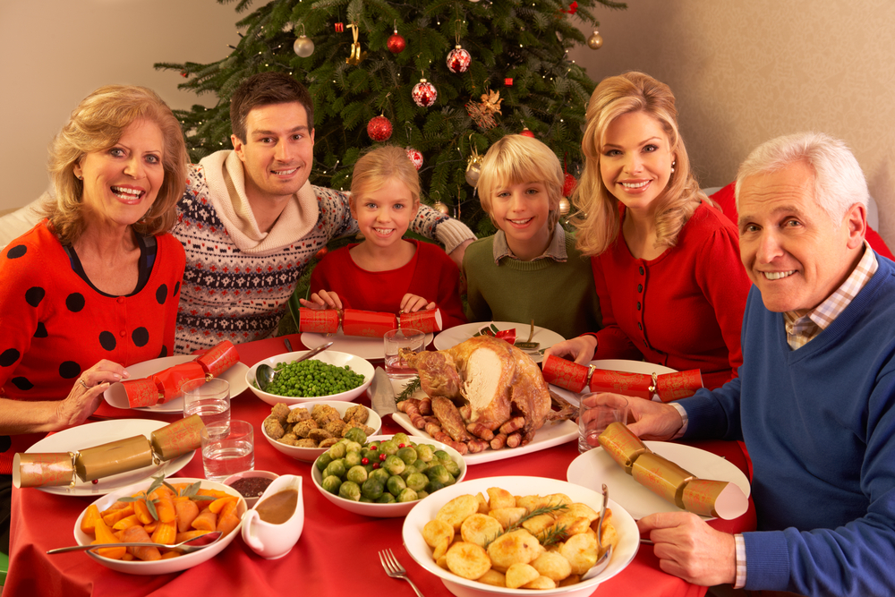 Large family sitting around a Christmas dinner, with decorations in the background.