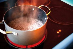 a pot on a stove, bubbles and steam rising