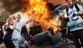 A riot surrounding a burning car. People look excited and are embracing chaos.