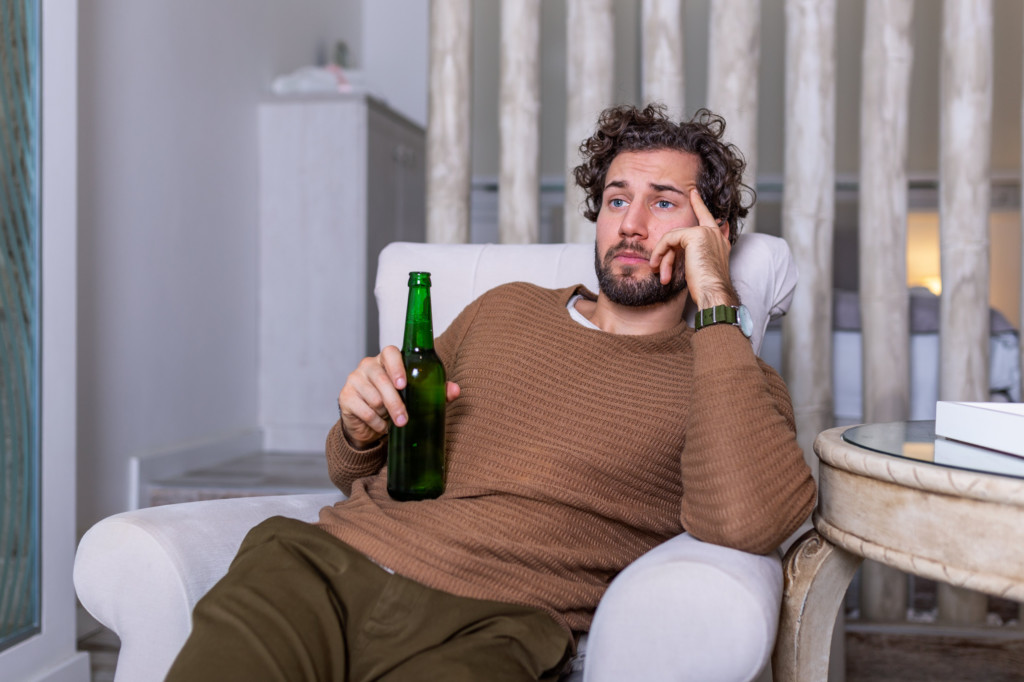 A sad looking man holding a beer staring whistfully at the TV