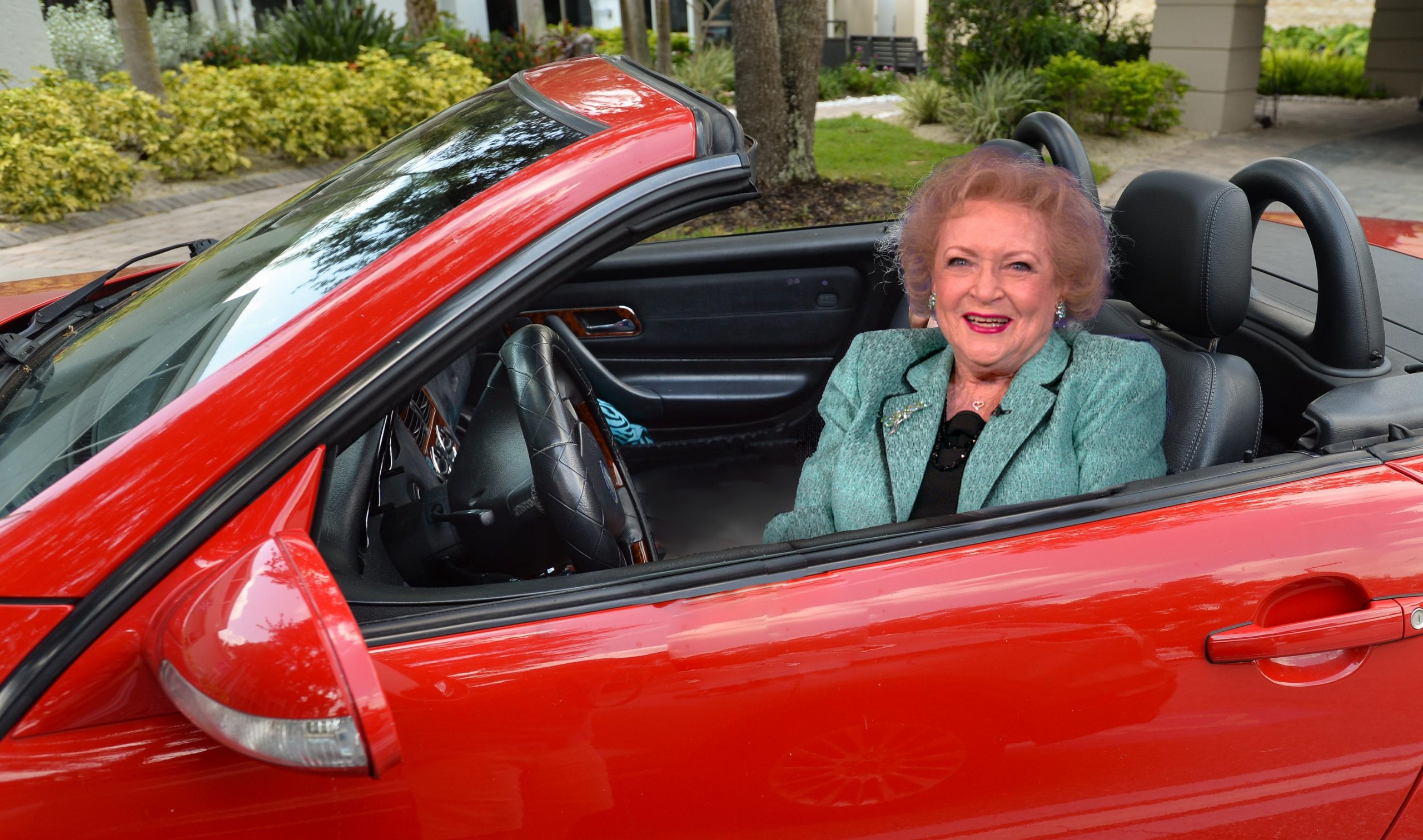A very self-satisfied looking Betty White sitting in a red Ferrari.