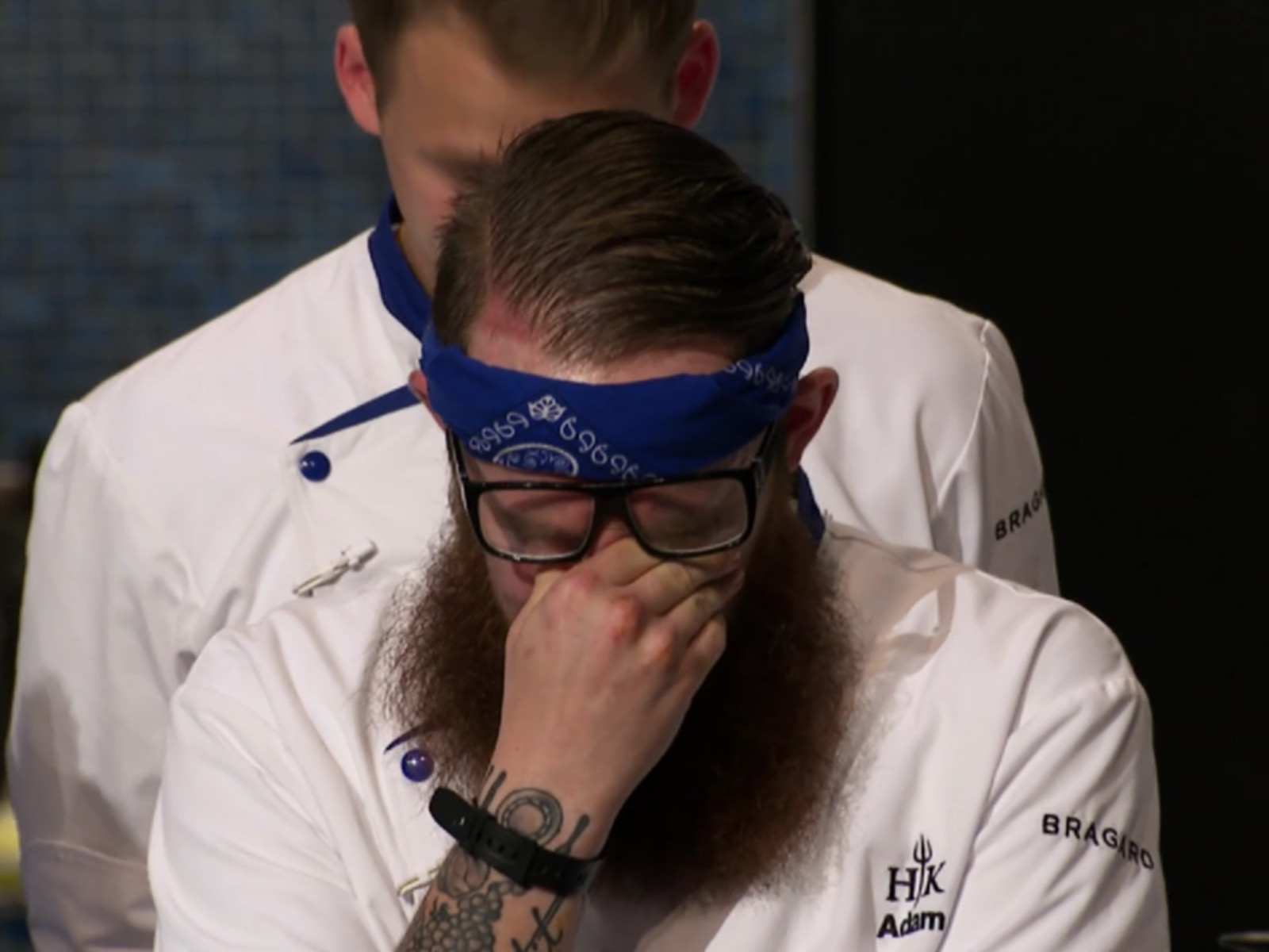 Distressed male reality show contestant covering face