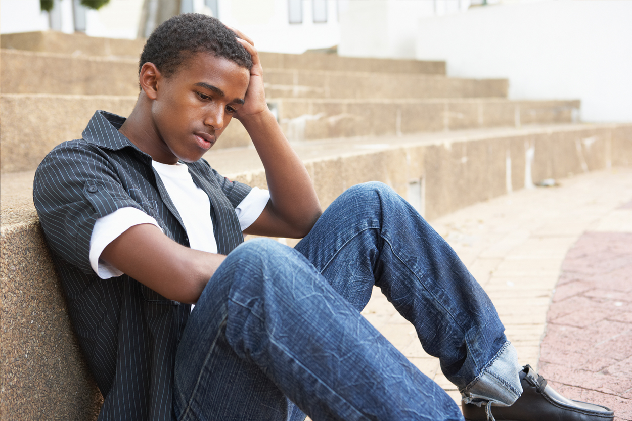 A sad looking college student sitting on some steps looking dreadful.