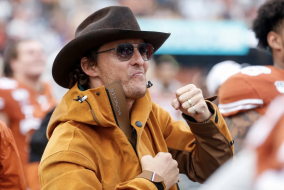 Matthew McConaughey looking excited and wearing a cowboy hat