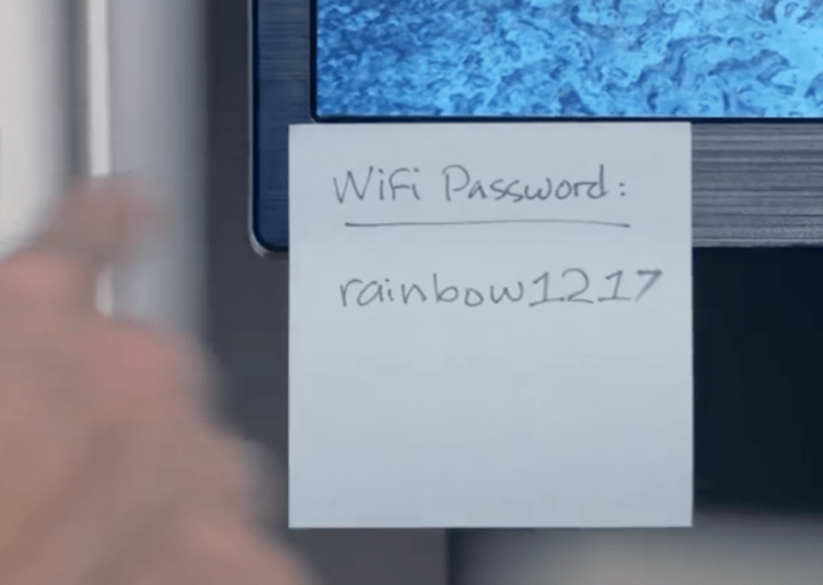 """A sticky note stuck to a computer reading """"Wifi Password: rainbow1217"""""""