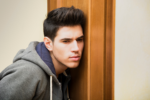 I man suspiciously pressing his ear to his roommate's door