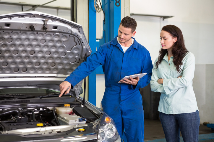 Mechanic showing female customer the problem with her car