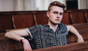 A young man on a church pew with a sour look on his face