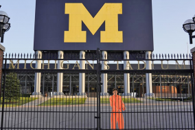A man in an orange jumpsuit behind the gates of the Ann Arbor Football Stadium.