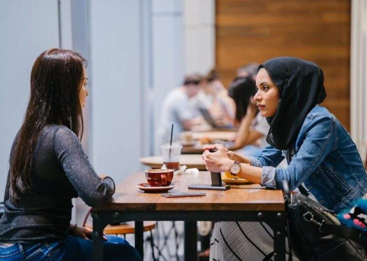 Two women have a conversation at a coffee shop.