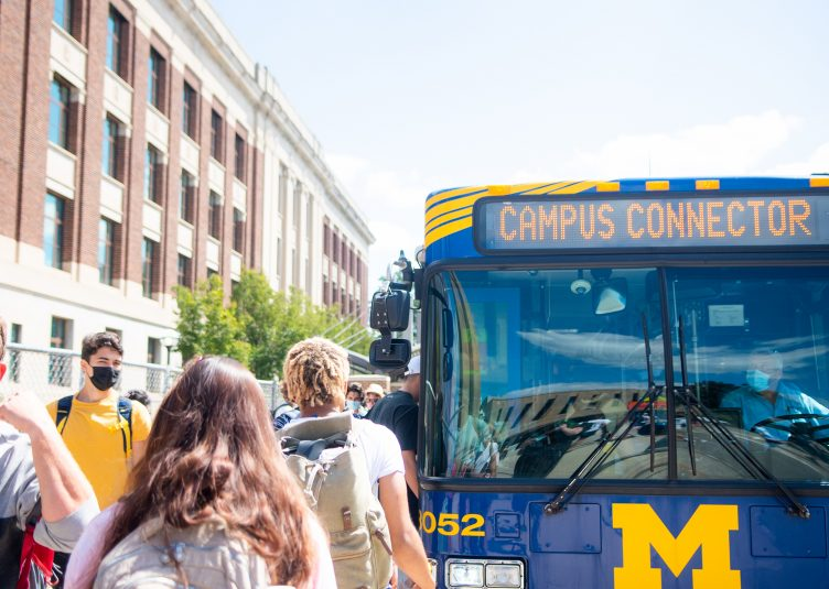 Several students are walking towards a Campus Connector bus.