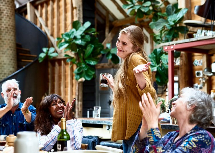 A woman is shrugging at a lunch while some older people are clapping?