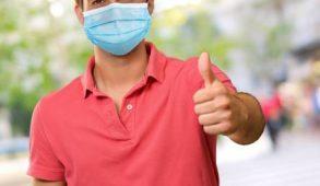 "Man wearing mask making ""thumbs up"" sign"