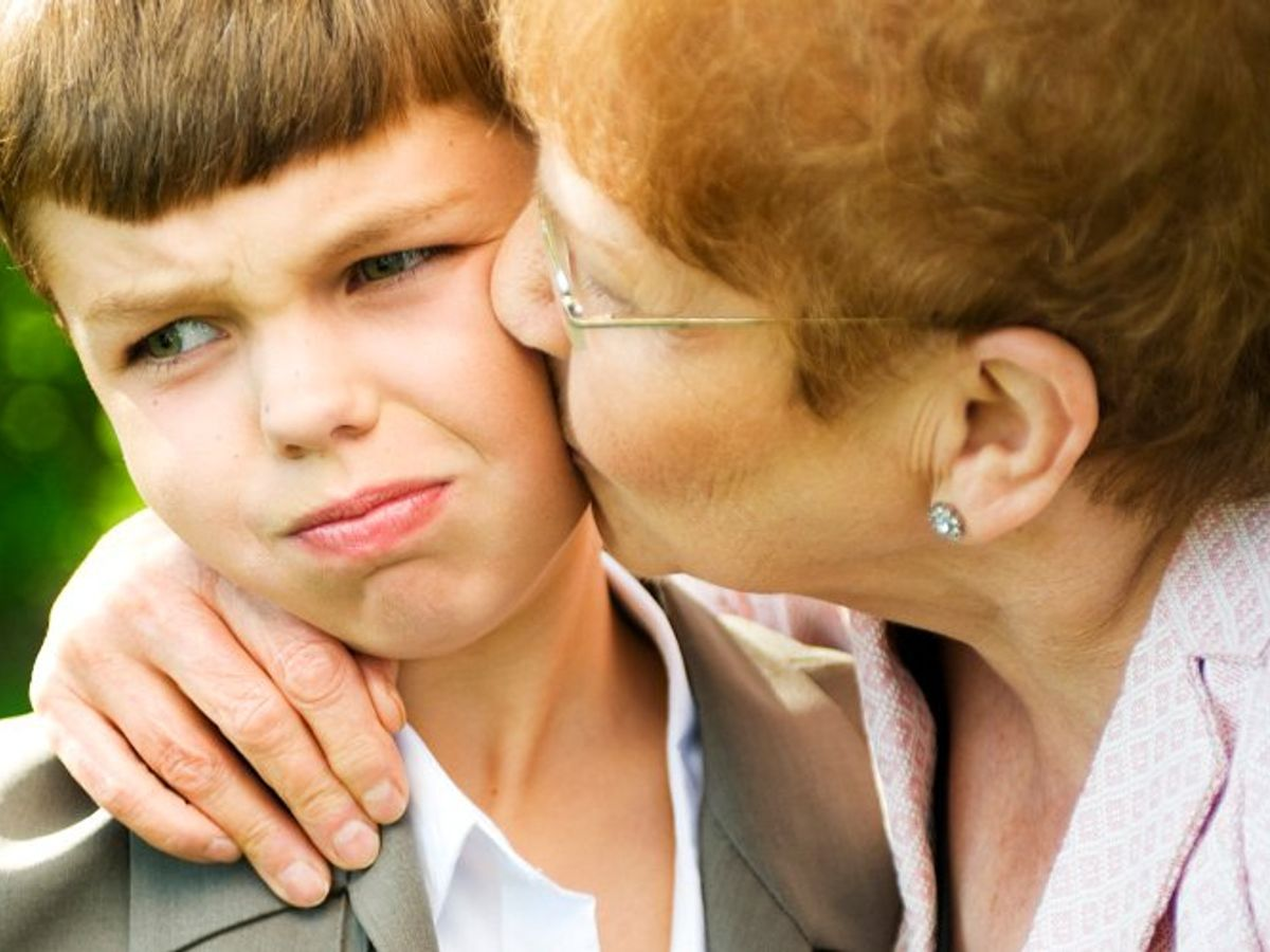 grandmother kissing a reluctant grandson on the cheek