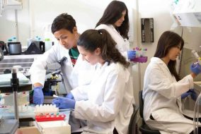 Four scientists wearing lab coats and gloves in a lab