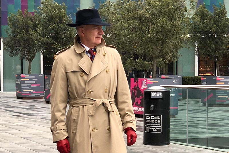 A conspicuous looking man in a hat and tan trench coat.