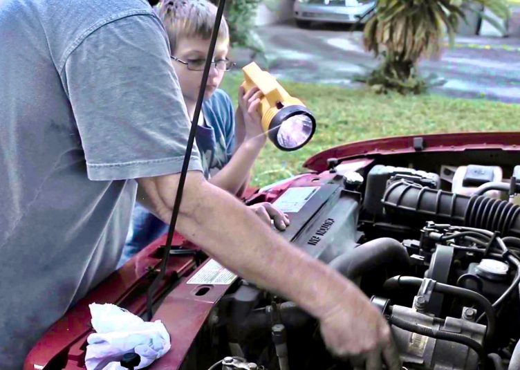A son holds a flashlight for his father, who is working on a car.