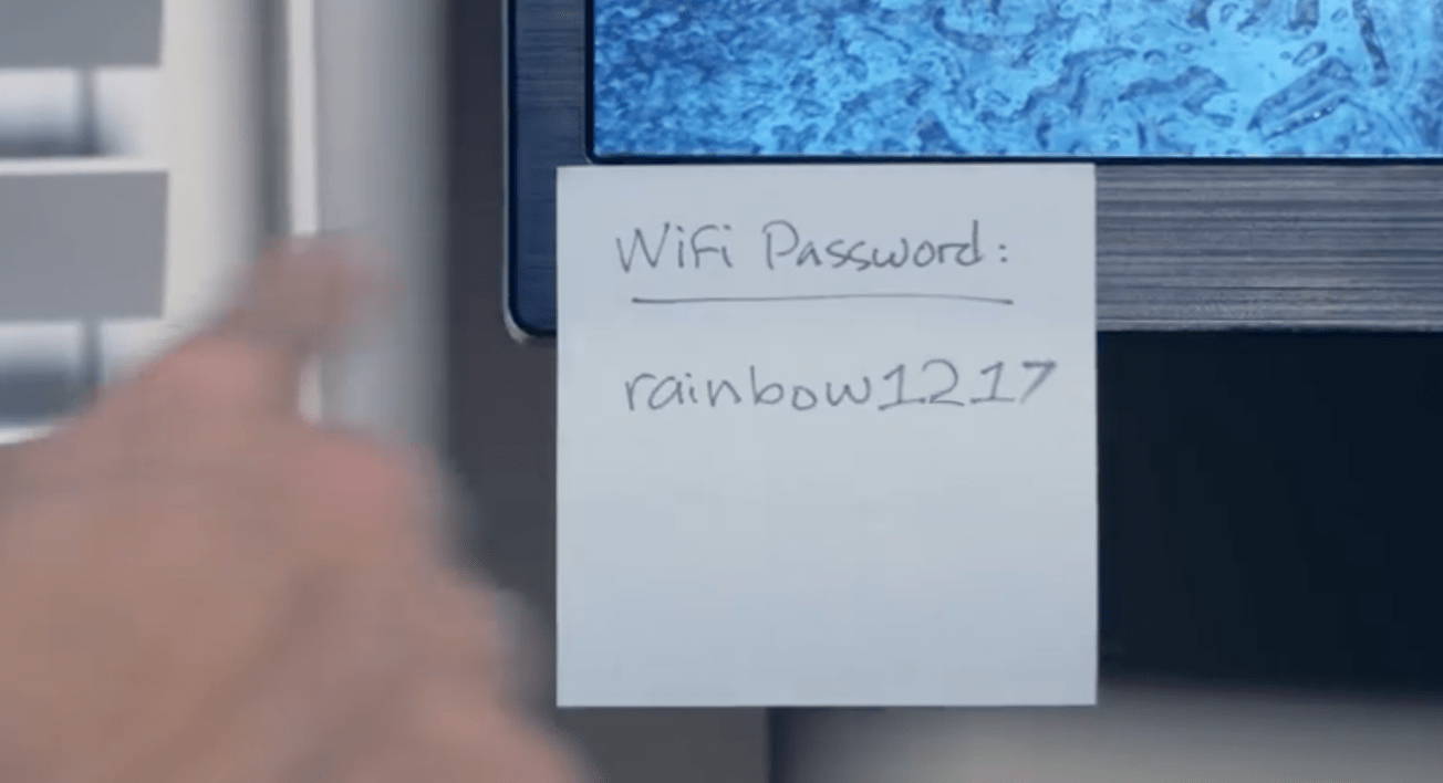 "A sticky note stuck to a computer reading ""Wifi Password: rainbow1217"""