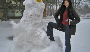 A large snowman with comically large and censored genitalia, and a woman proudly posing next to it.