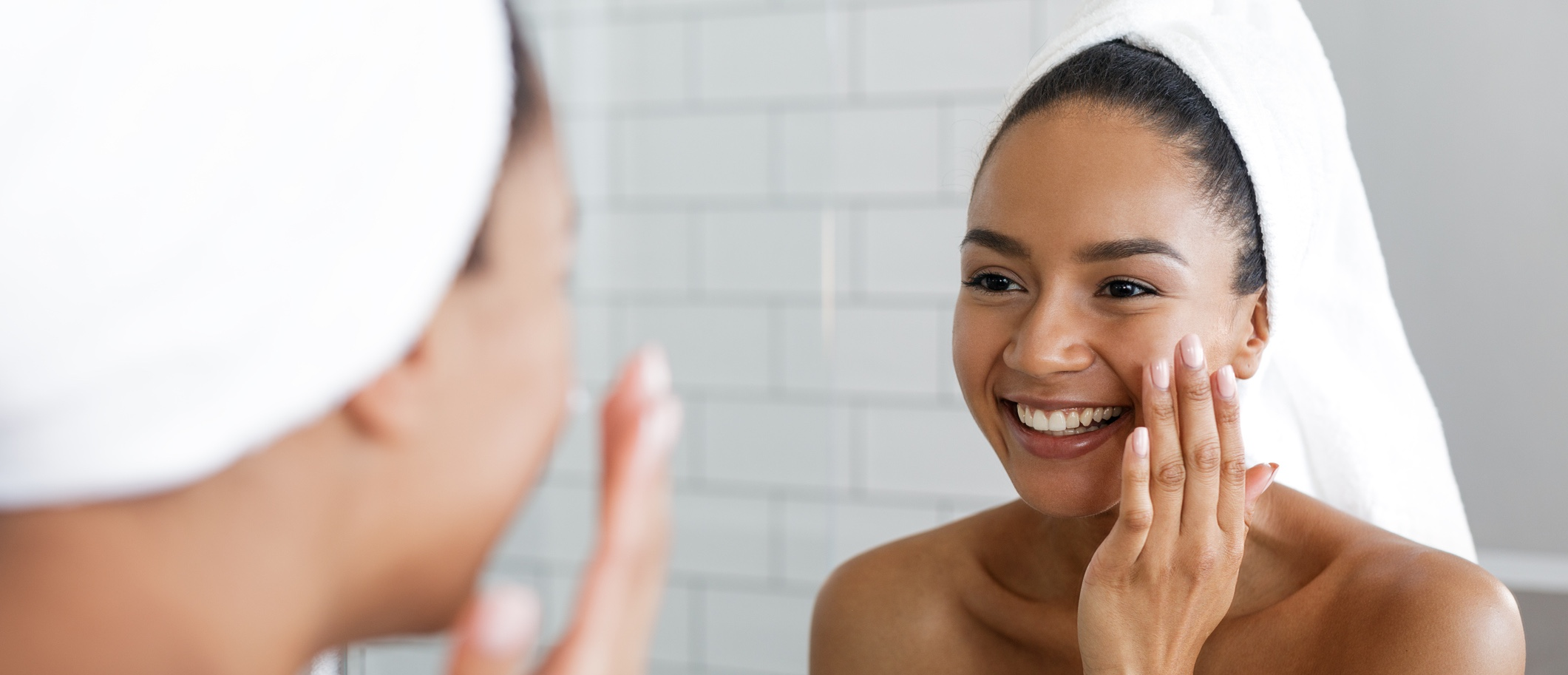 Happy woman putting on facial moisturizer with hand in bathroom mirror