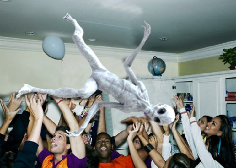 An alien crowdsurfing at a house party.
