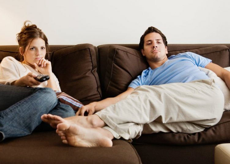 Bored man and woman lounging on couch