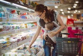 A woman at the grocery store with a baby.
