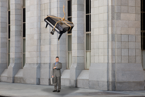 I piano dangling precariously dangling above a man not paying attention to it