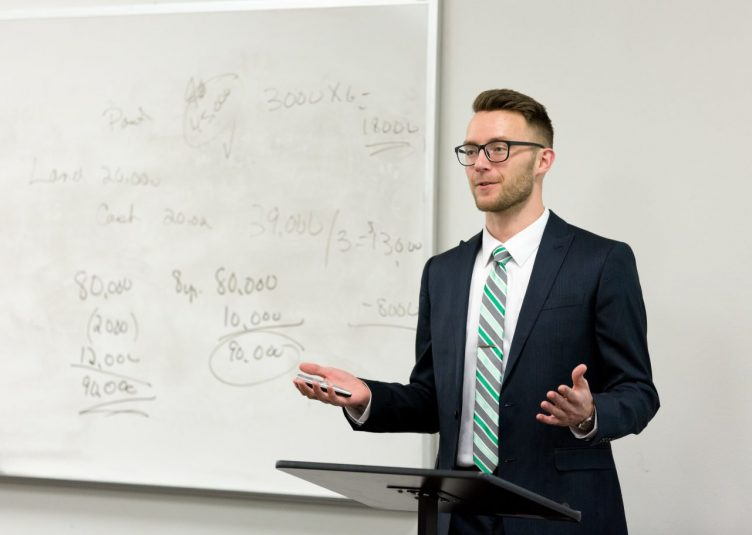 A pretentious looking man standing in front of a whiteboard