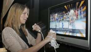 A woman uses a wireless controller to play a boxing game on a Nintendo Wii