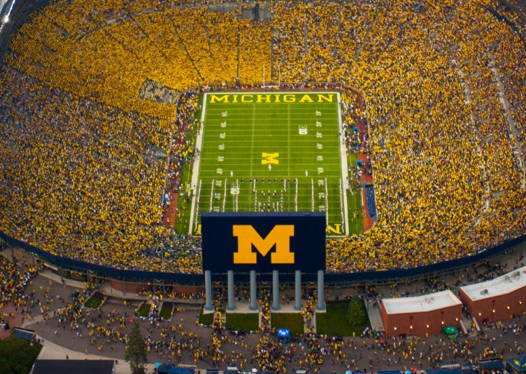 Overhead shot of a very filled Big House at night. Michigan logo is visible